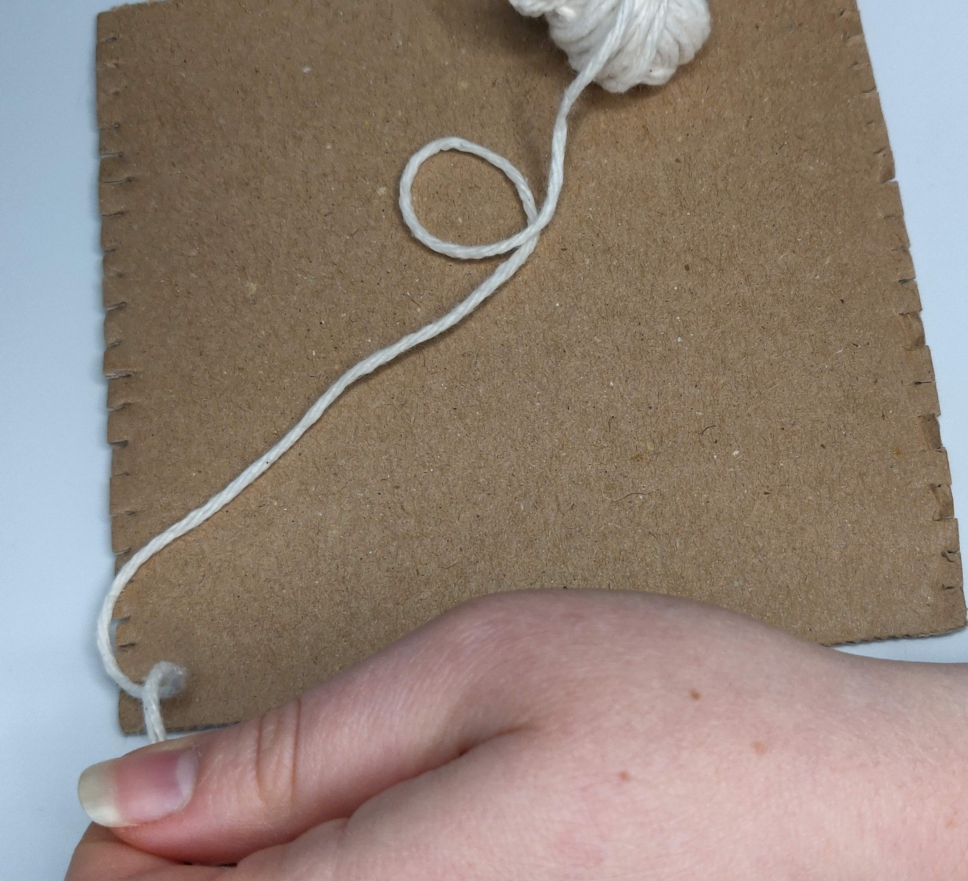 A simple cardboard loom with a small ball of yarn sitting on top, and a hand ready to begin warping the loom