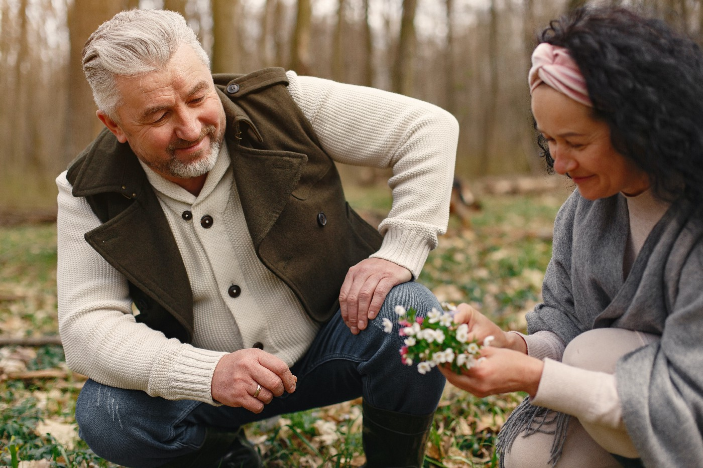 Middle aged man and woman kneel in a forest floor. The woman holds a bouquet of hand picked flowers. They look calm and happy.