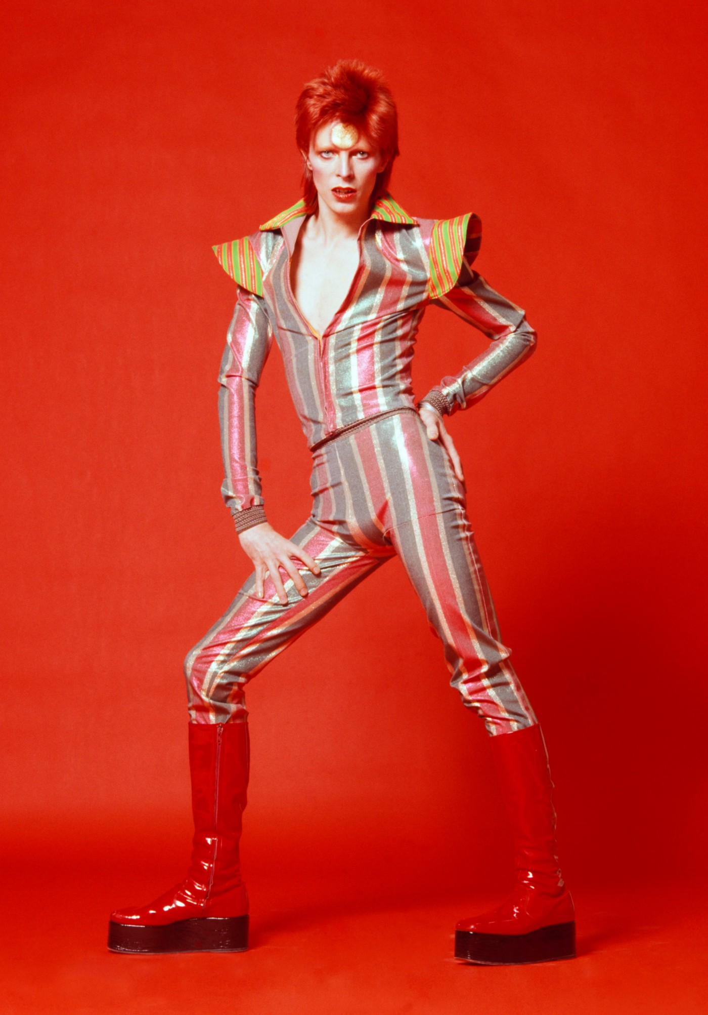 David Bowie wearing a striped jumpsuit and red platform boots against a red background.