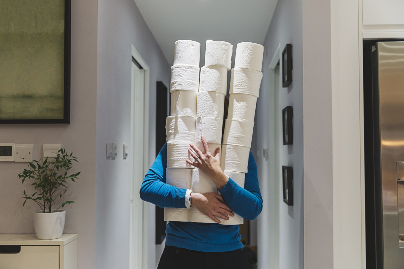 A photo of a person holding a tower of toilet paper rolls as they walk down the hallway.