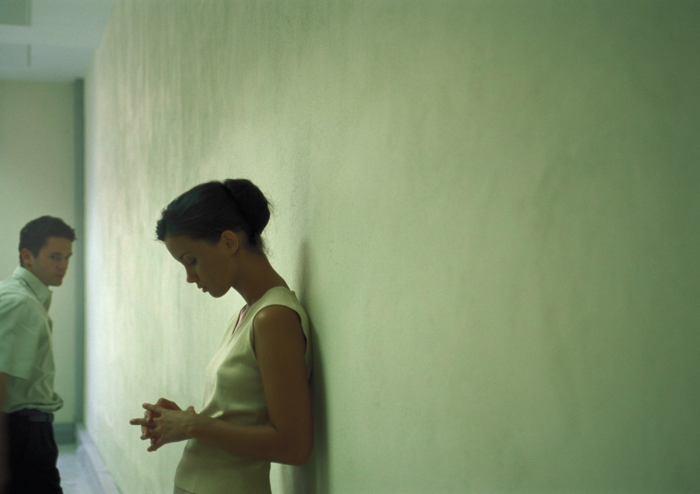 A photo of a woman leaning against a wall as a man looks back at her from the corner.