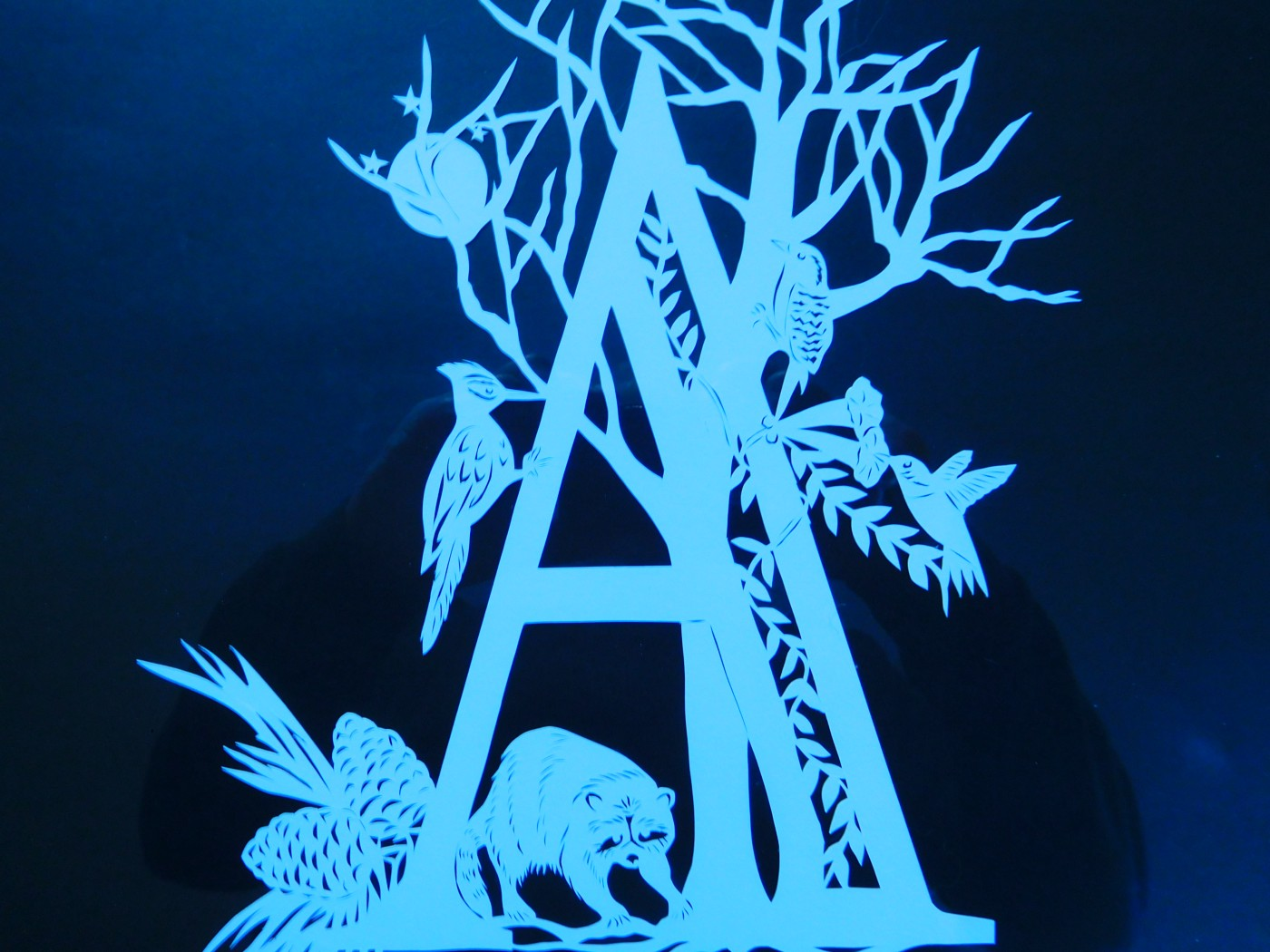 """two shades of blue papercut design for the initial letter """"A"""" with a tree and various birds plus a full moon behind the branches and a raccoon at bottom"""