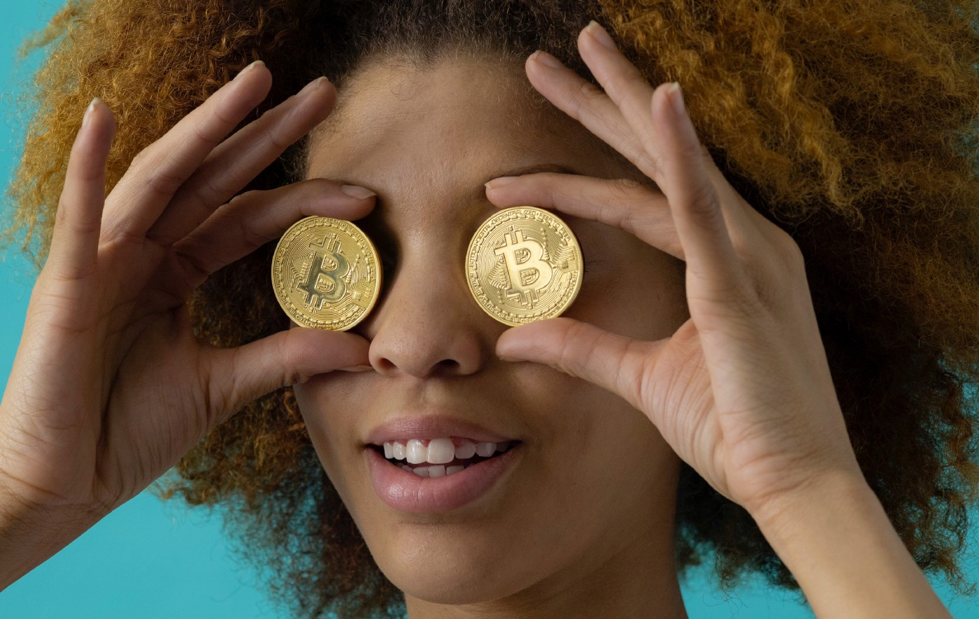 Woman holding two Bitcoin representations in her eyes. What is Bitcoin?