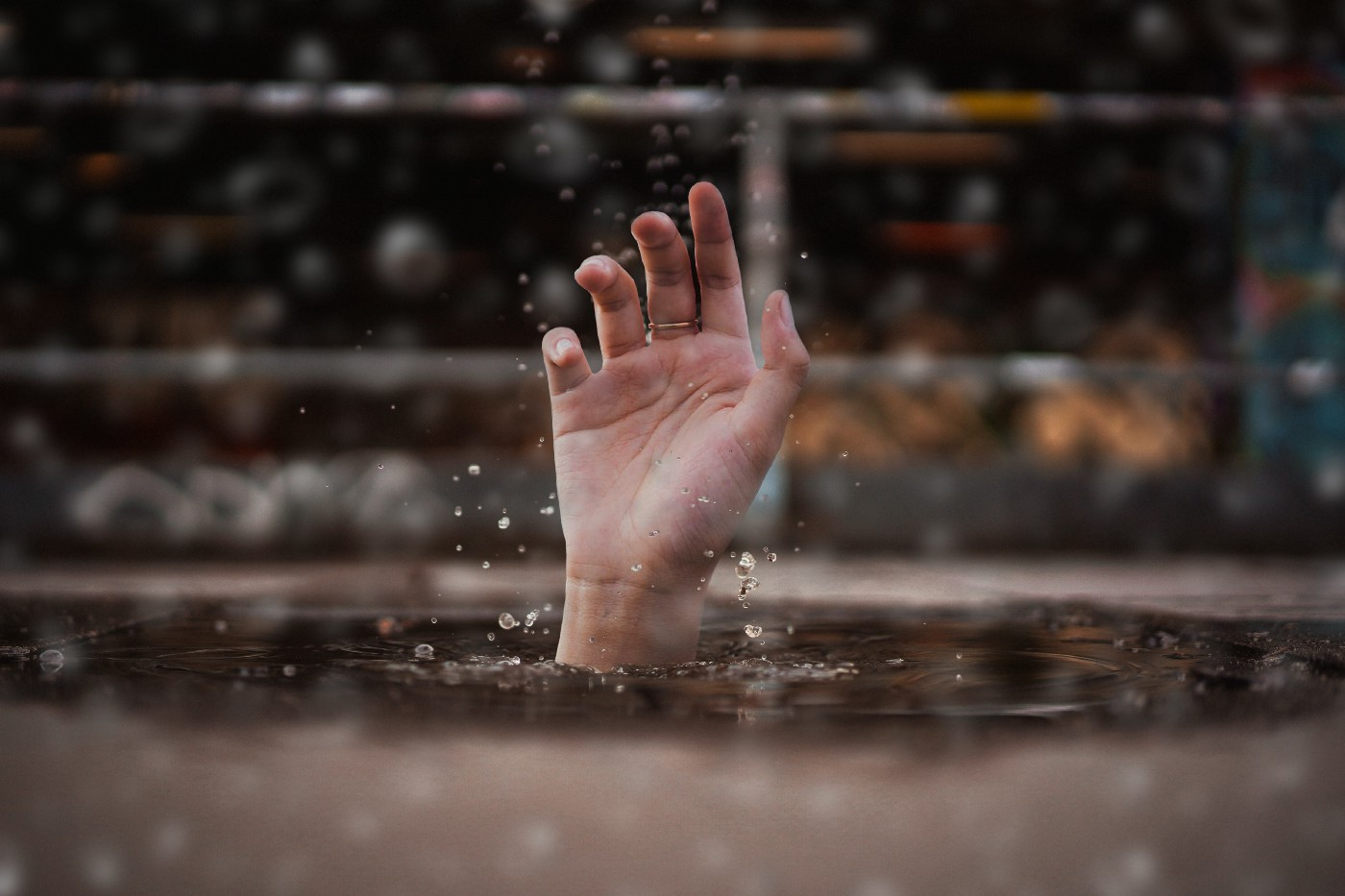 A picture of a hand sticking out of the water as though they're drowning.