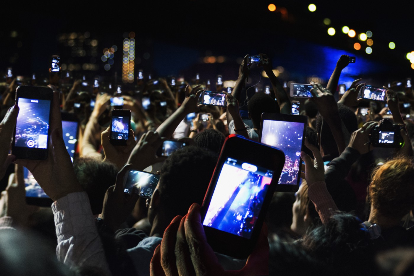 A photo of a sea of phones recording a scene at a concert at night.