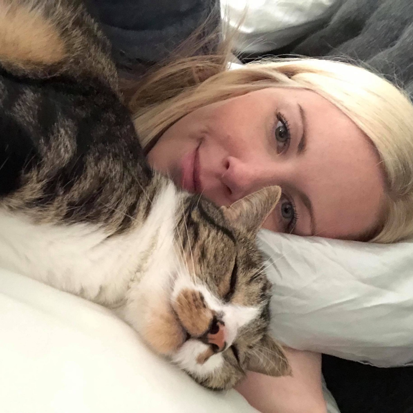 The author lying in bed with her cat sleeping in front of her.