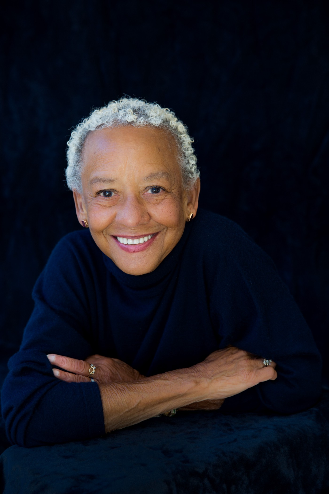 Portrait photo of Nikki Giovanni against a black background.