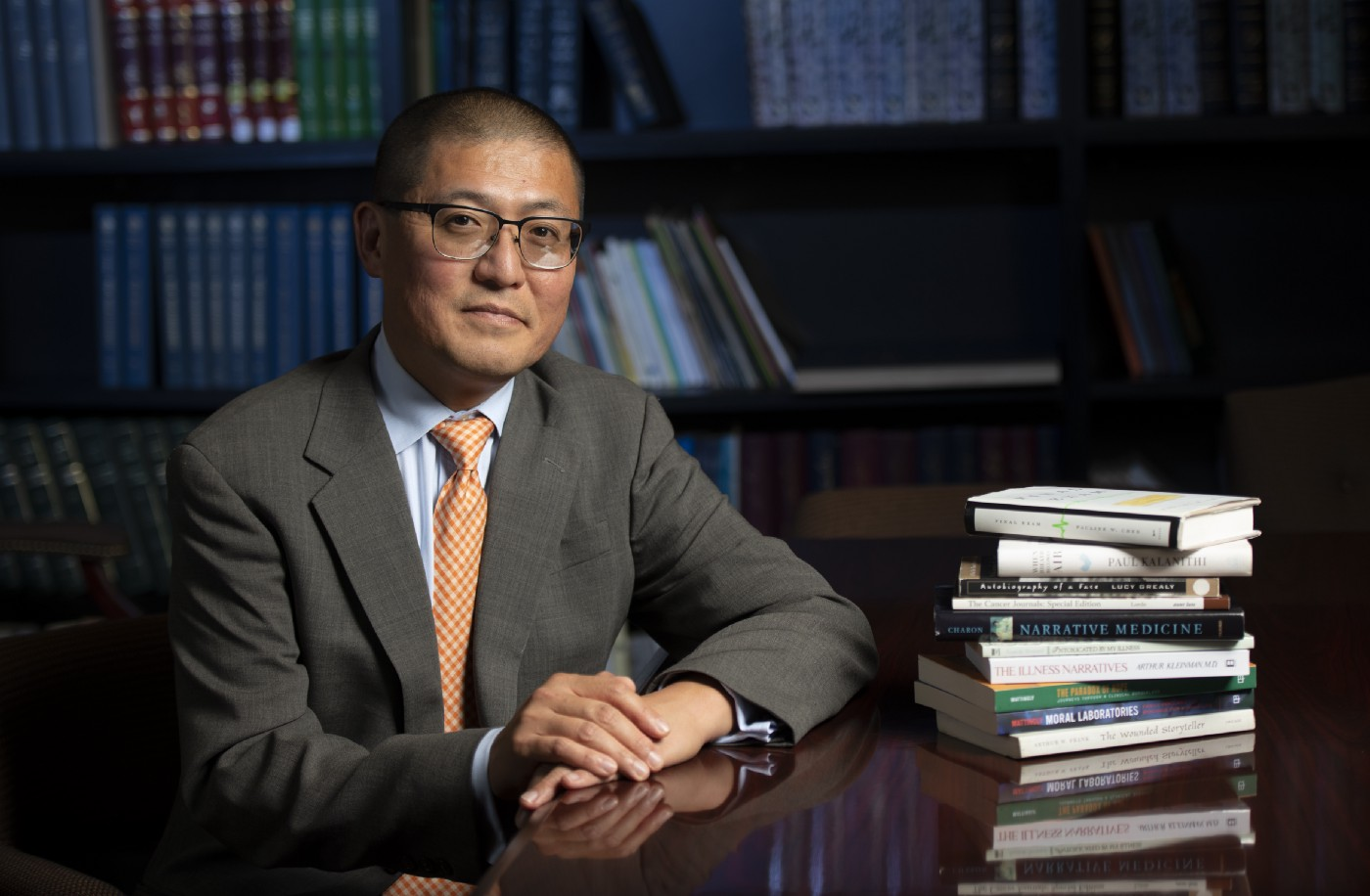 James Kyung-jin Lee rests his hands on the table in front of him, which is stacked with books. Behind him is a book case.