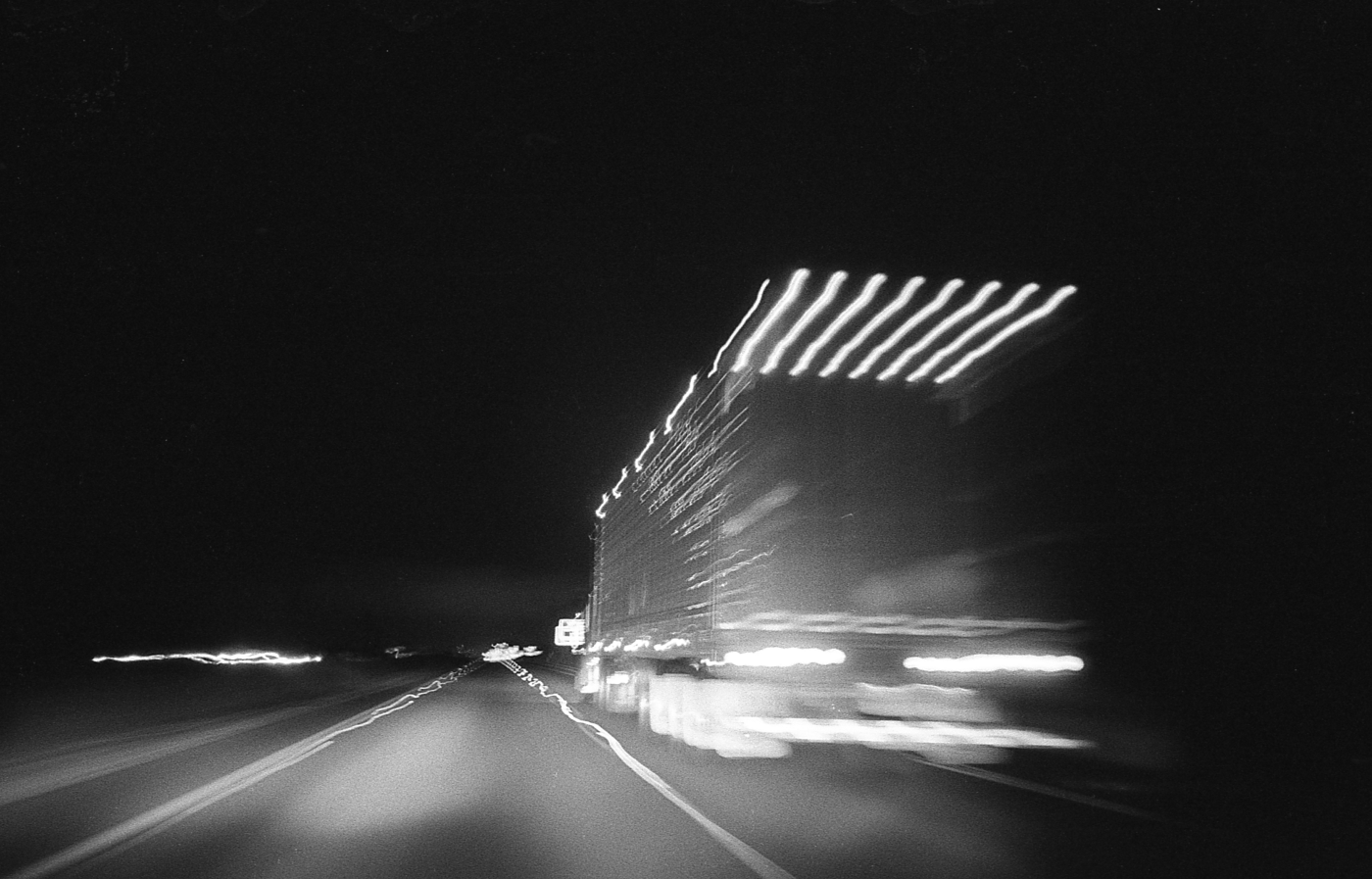 A photo of a big rig speeding down the highway at night.