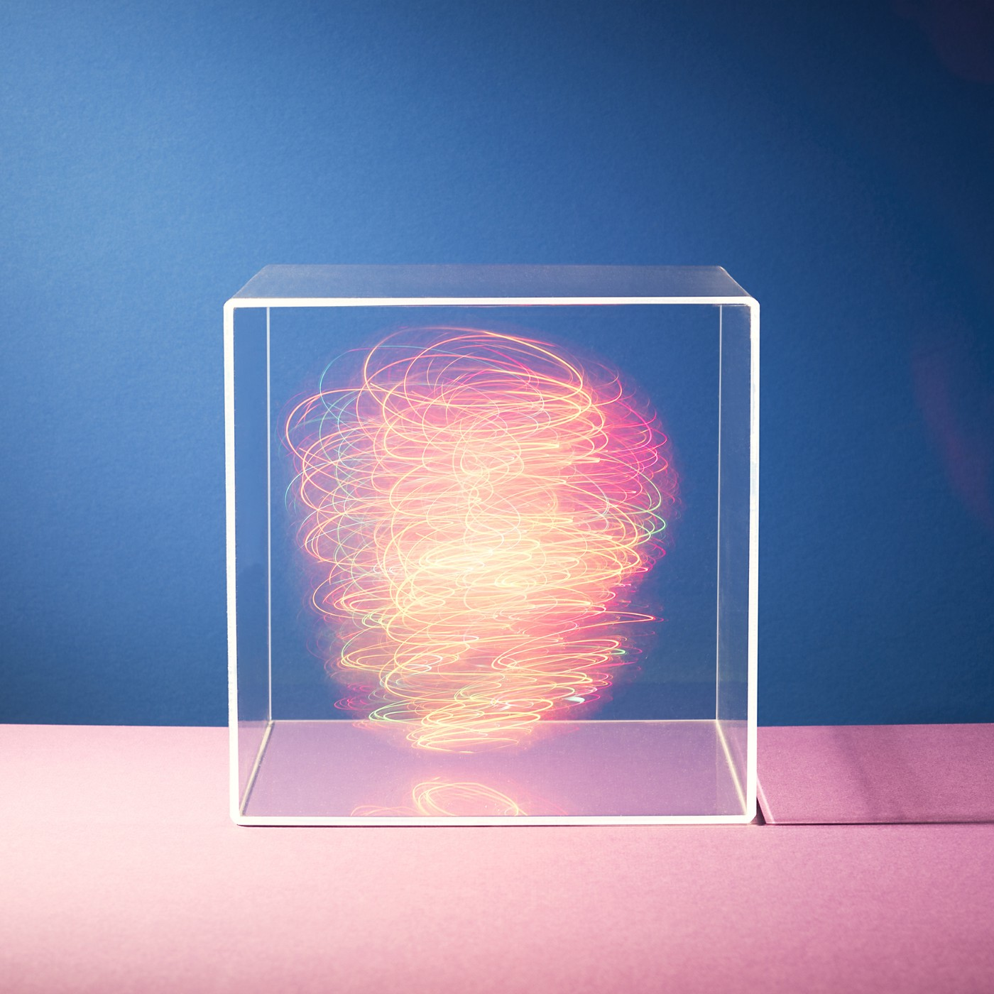 Colorful lights swirling around inside a clear box.