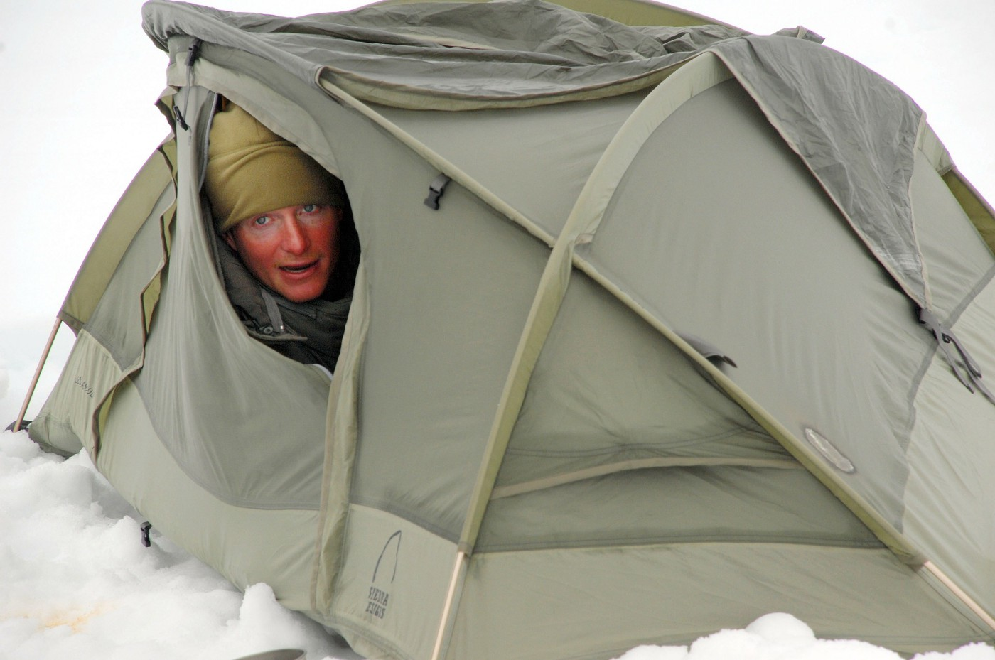 A woman with a sunburned face and winter hat peeking out of a tent surrounded by snow.