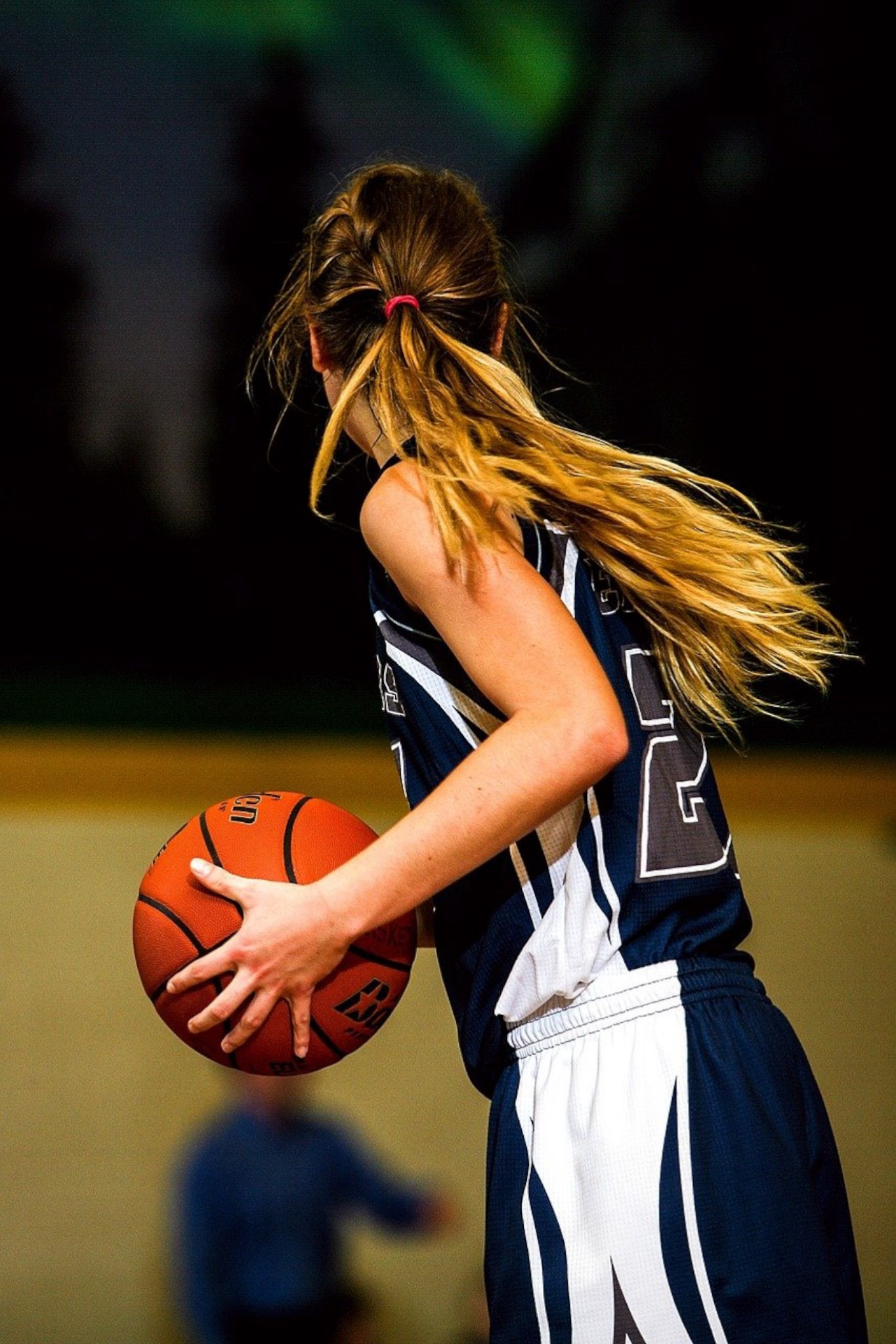Color photo of a young  blond woman with her hair tied back in a ponytail, wesringa black and white team uniform, holding a basketball, contemplating her next move.