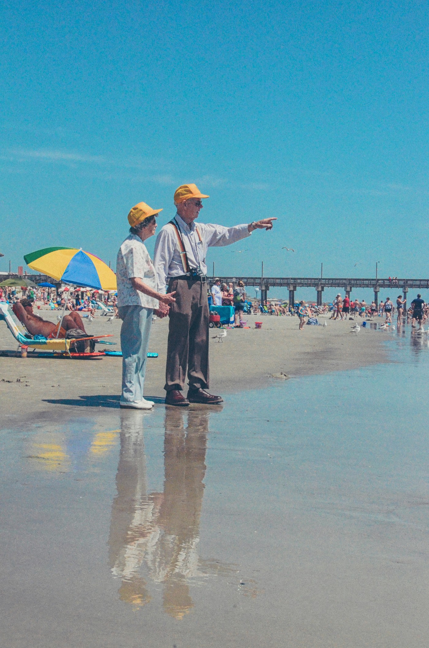 Old man and wife at beach wearing yellow hats