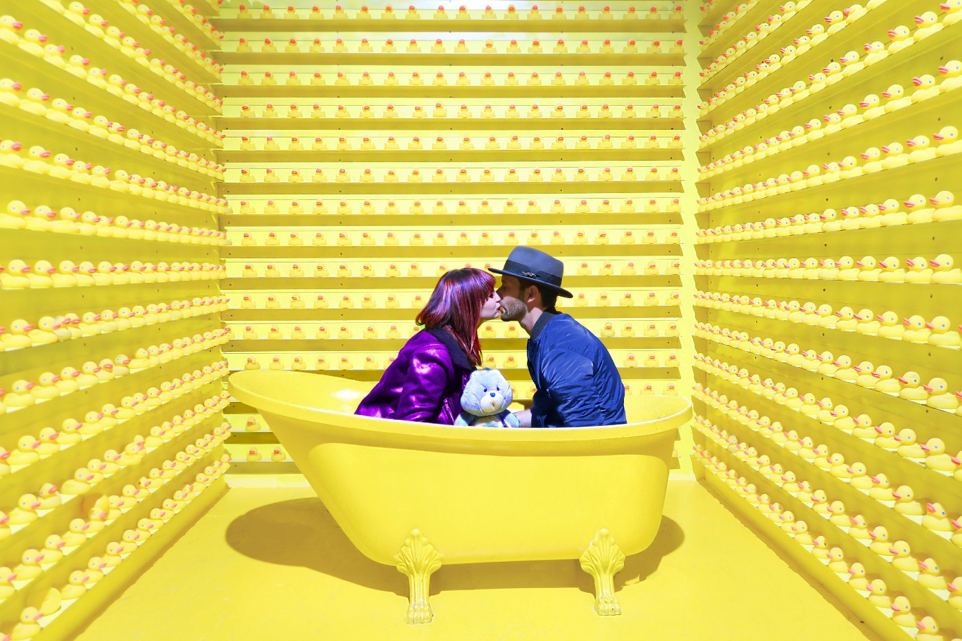 Happy couple kissing in tiny yellow room.
