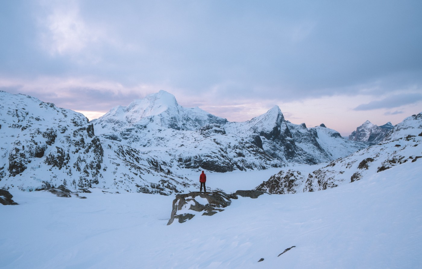 Person standing in front of snowy mountains