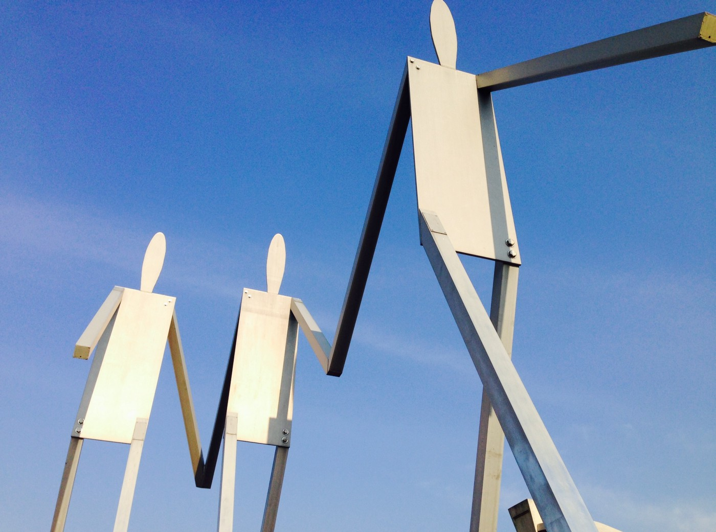 A photograph of a public sculpture featuring three silver metallic human figures striding forward together, hand in hand, tall against the background of a clear blue sky.