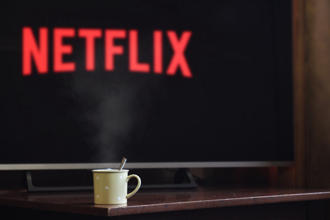 """A steaming off-white cup sits on a dark, reddish wood table top, with a TV with """"Netflix"""" in red letters in the background"""