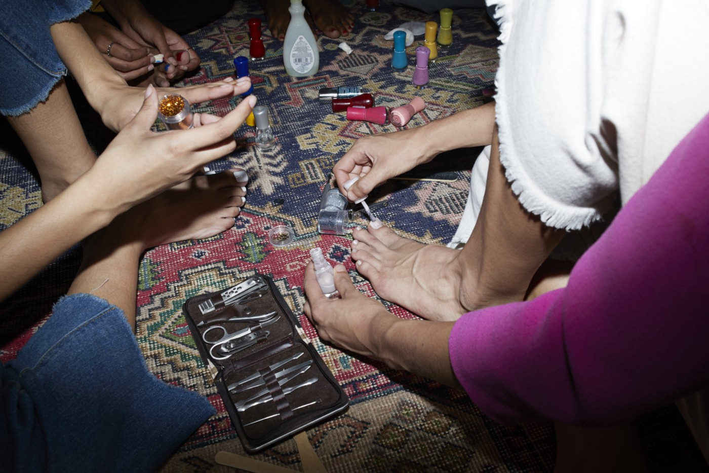 Low section of female friends applying nail polish while sitting on carpet at home.