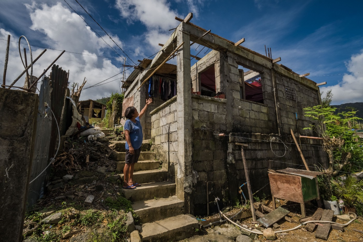 Rosalie Triste, who is 47 years old, points out the areas of damages in her home in Catanduanes, Philippines on 15 December 2020, following the devastating effects of Typhoon Goni.