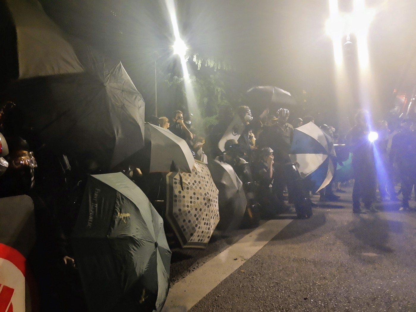 Protesters stand in a line on the street and hold up umbrellas as shields. It obscures their faces