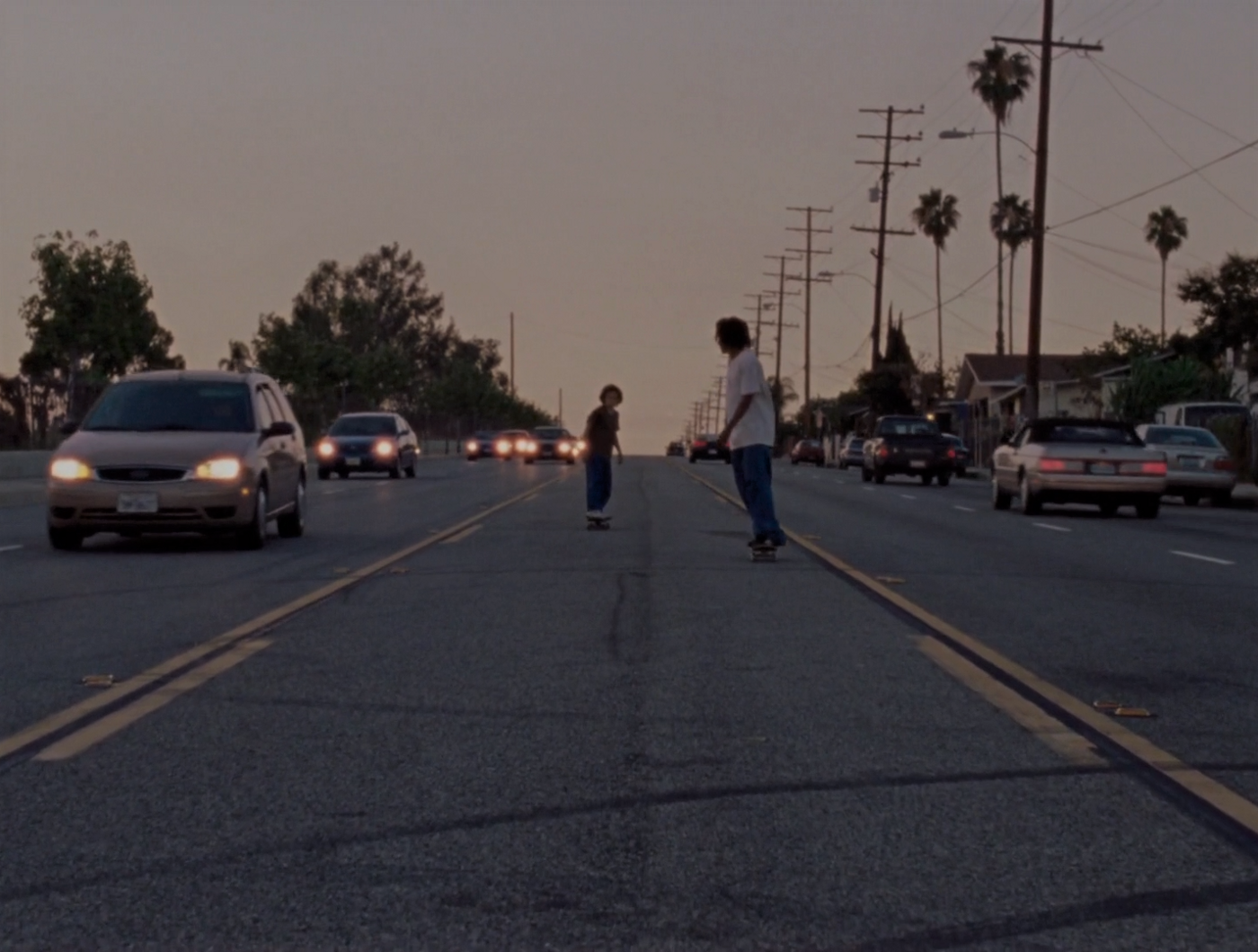 A black teenager and a white twelve year old skateboarding down the middle of a street on a busy road.