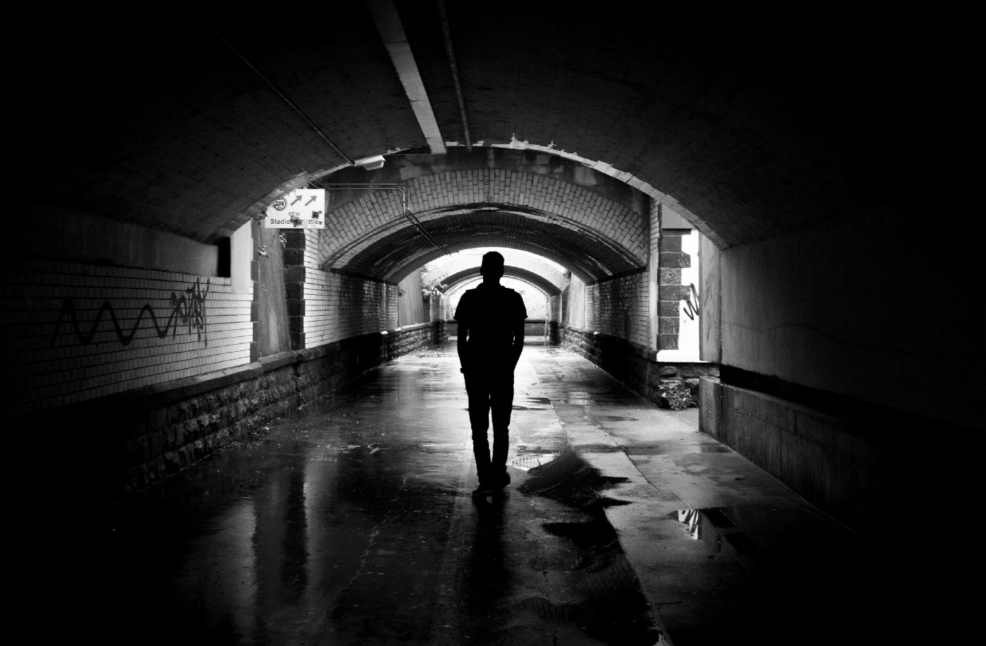 A person walks in a dimly lit subway. The photograph appears to be black and white due to the lighting. It is very dark, with a spotlight on the center of the image and black around the edges.