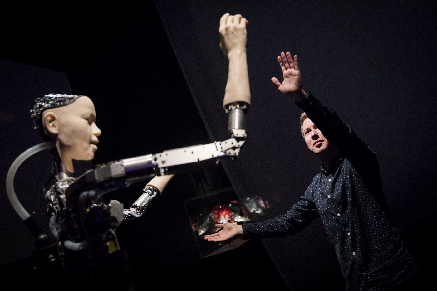 A person mirroring the movements of the humanoid robot Alter 3.