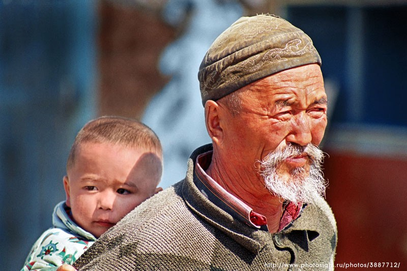 A child being carried by an old man in Eastern Qazaqstan.