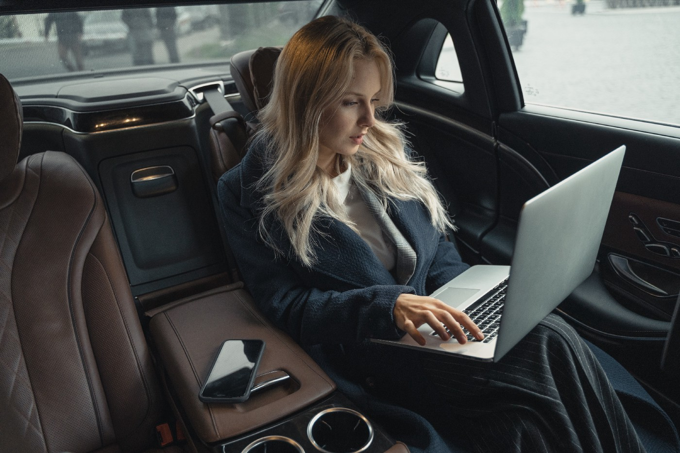 Woman working on her laptop while reclining in a luxury car. Leather seats.