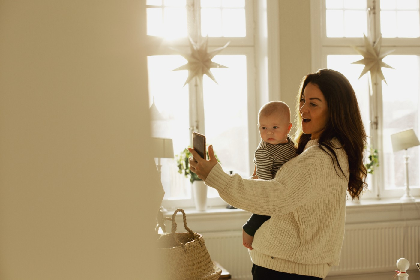 Mother holding baby son and taking a photo of something.