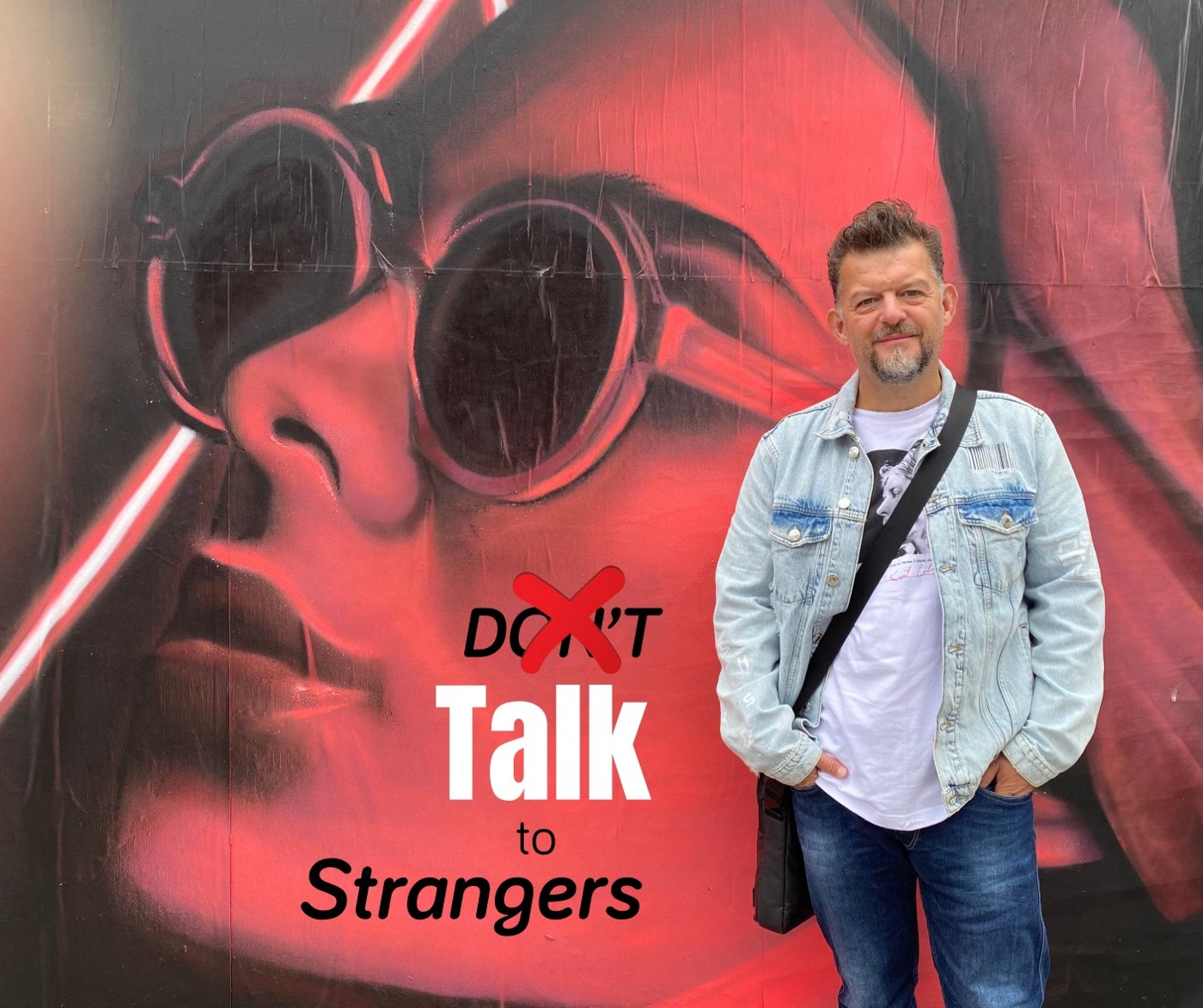 The author Stefan Thomas in front of a banner with the words Talk to Strangers behind him.