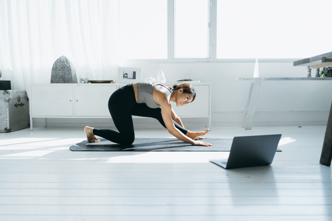 Young woman stretching on a yoga mat in front of a laptop.