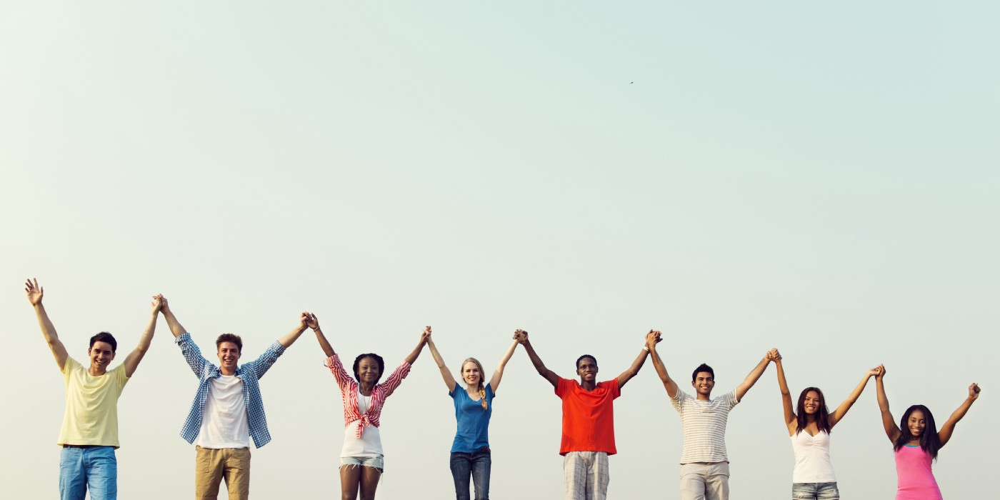 Eight people of different races and genders holding hands up in the air