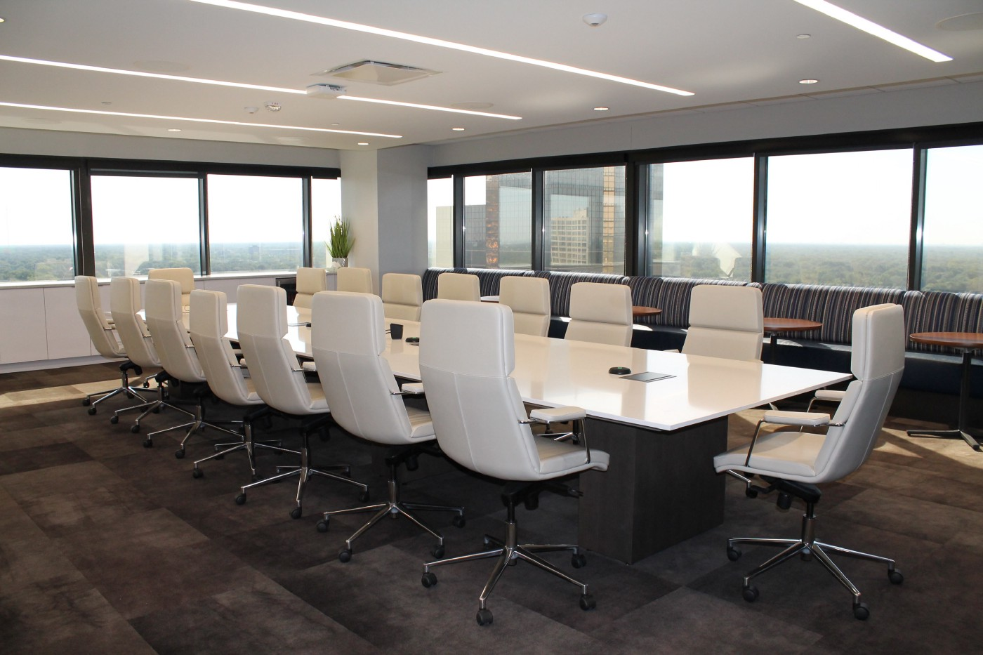 Boardroom inside sky scraper with lots of windows and white furniture, table and 15 chairs