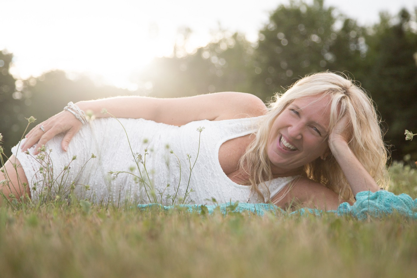 Liz Porter laying on her side in the grass in a white sleeveless dress laughing