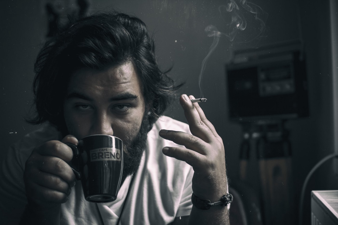 A man drinking coffee while smoking a cigarette