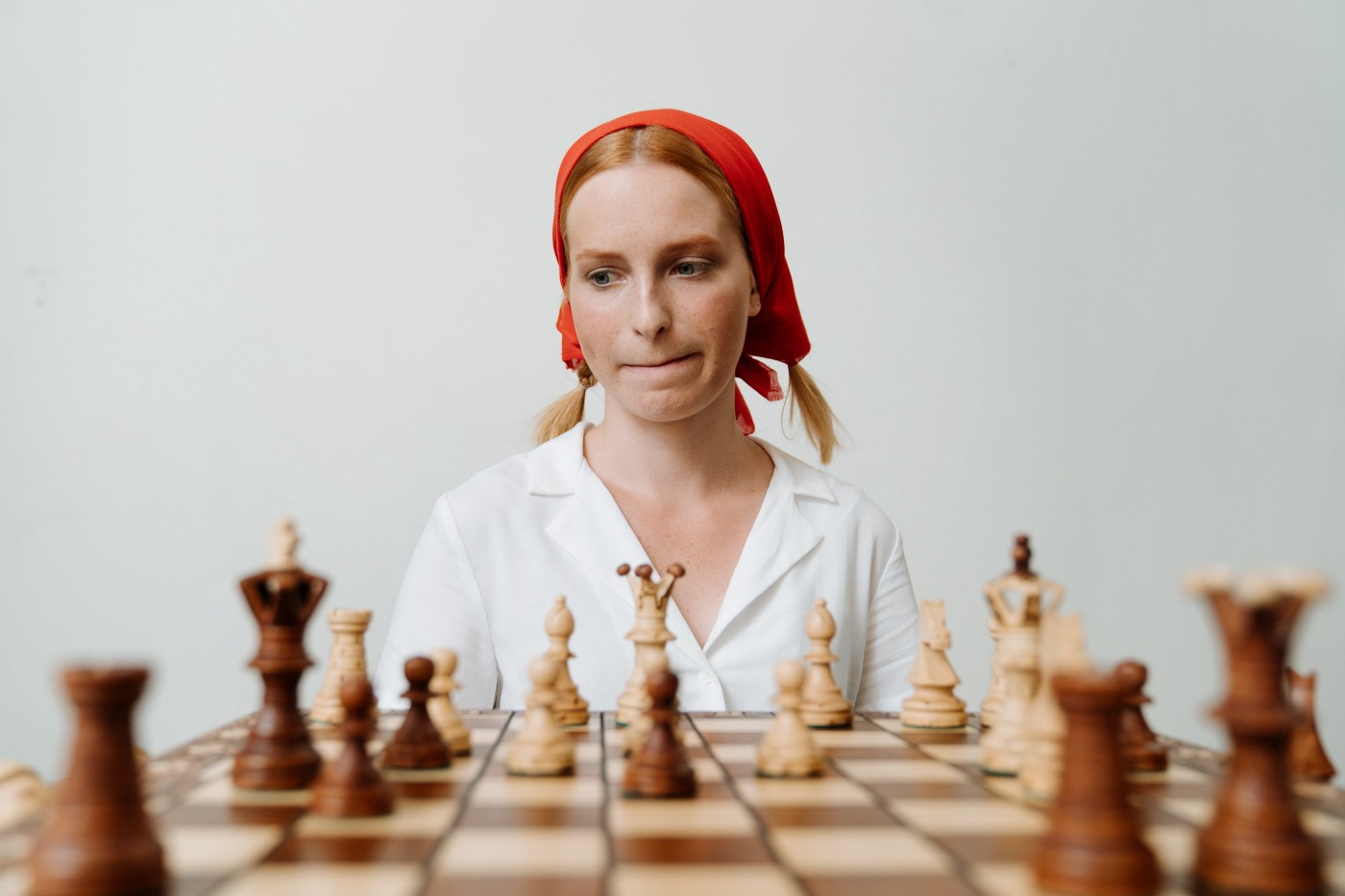 Woman staring at a chess board