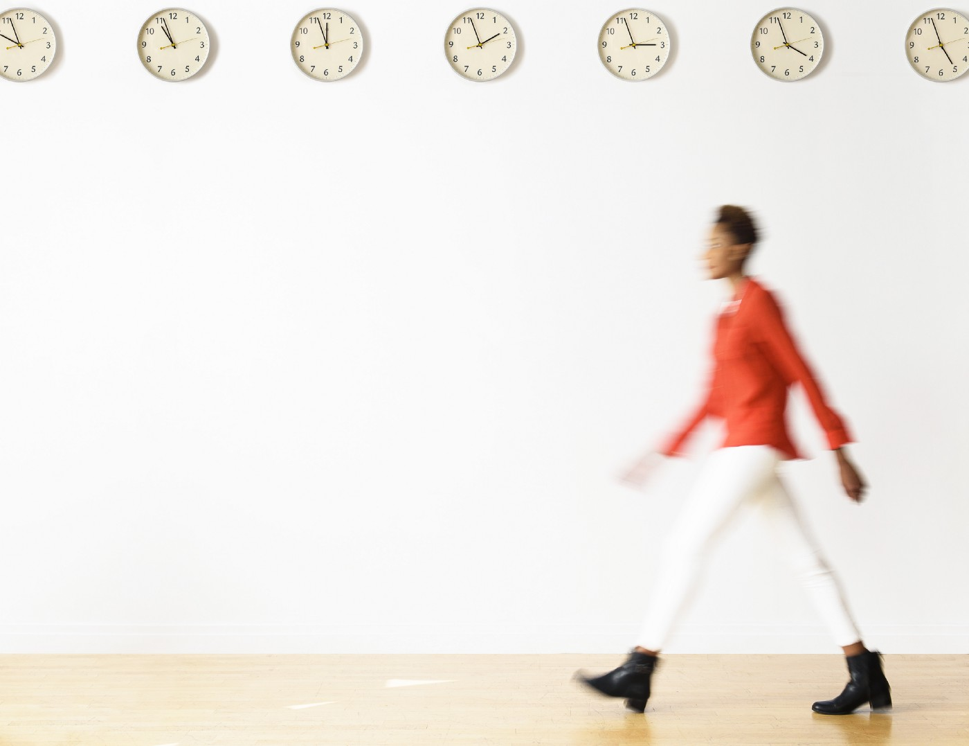 Blurry image of a woman walking past clocks.