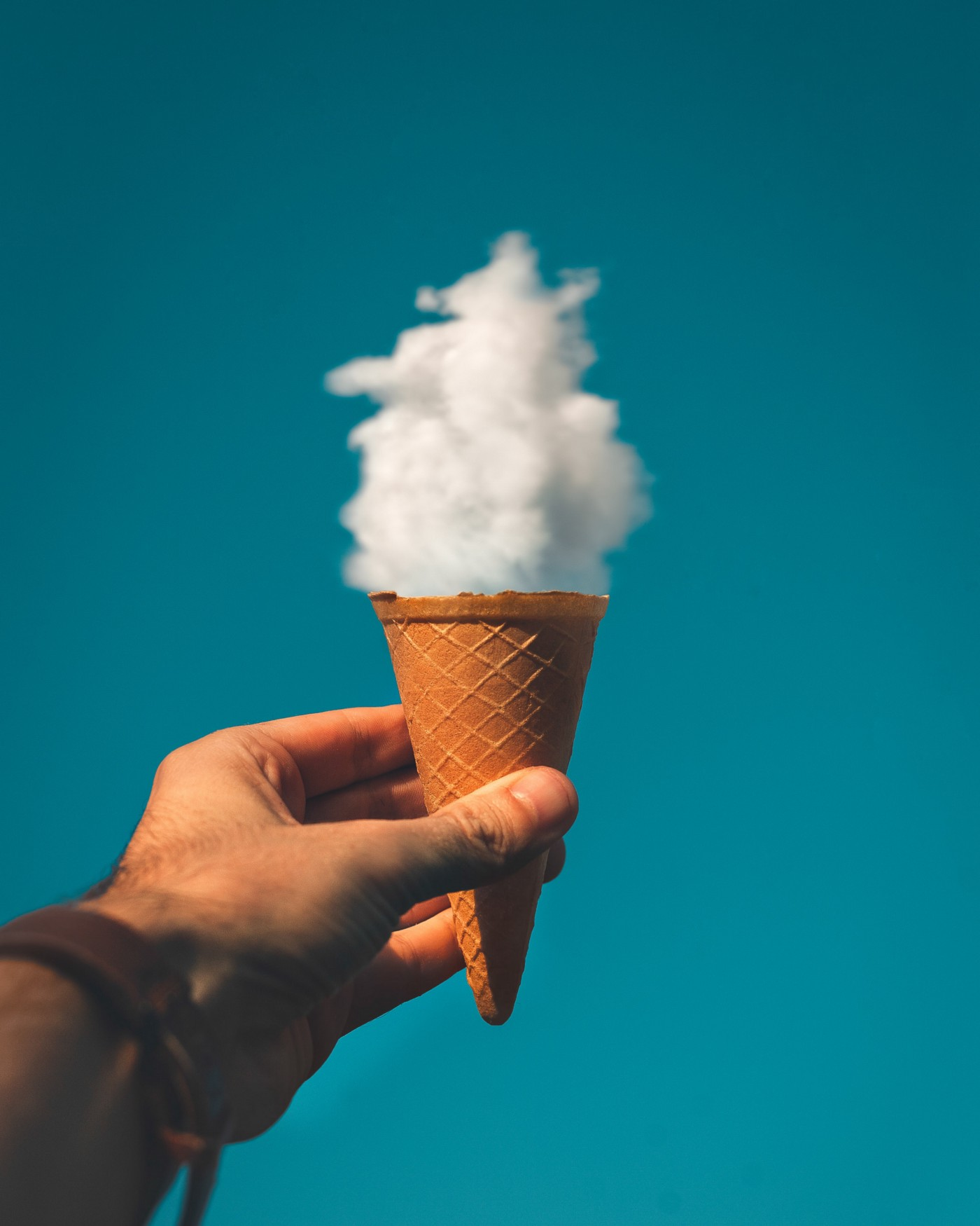 Ice cream cone being held up against a blue sky with a fluffy white cloud placed so it resembles ice cream in the cone.