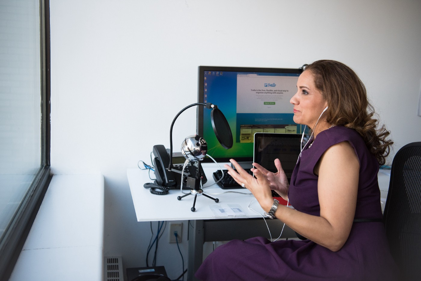 woman speaking into microphone in front of a computer with GitHub on the screen