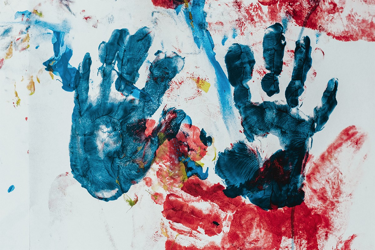 a pair of blue hand prints on a white wall with red smudges