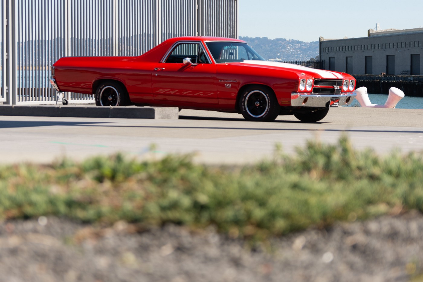 A red El Camino car in a parking lot on a sunny day