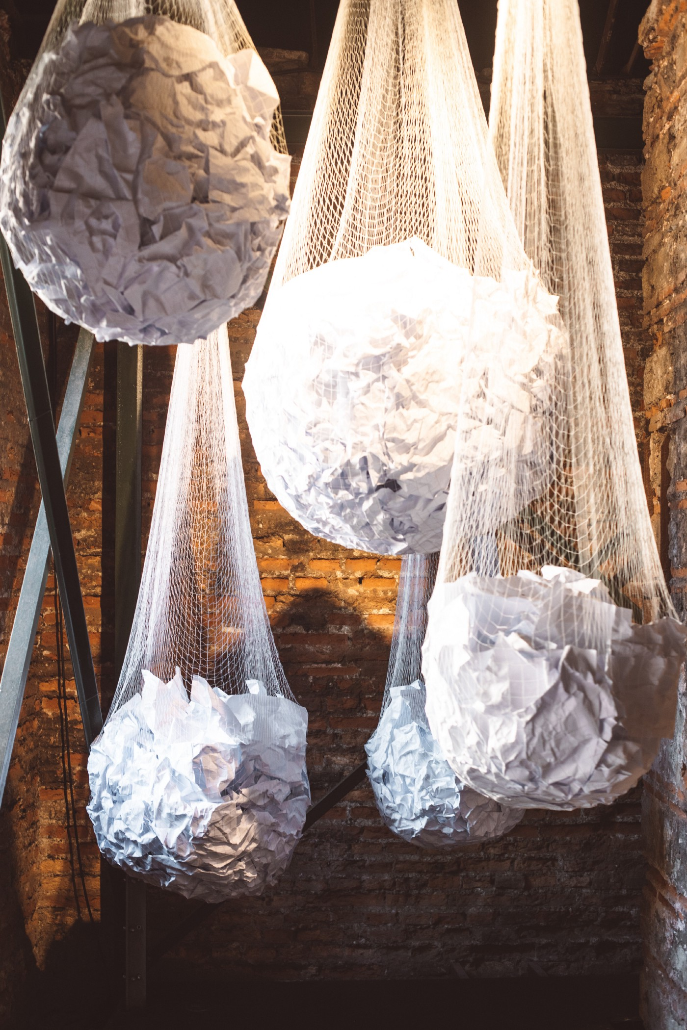 Rope bags of crumpled up white paper hanging from the ceiling. Background is industrial, yellowish brown brick wall.