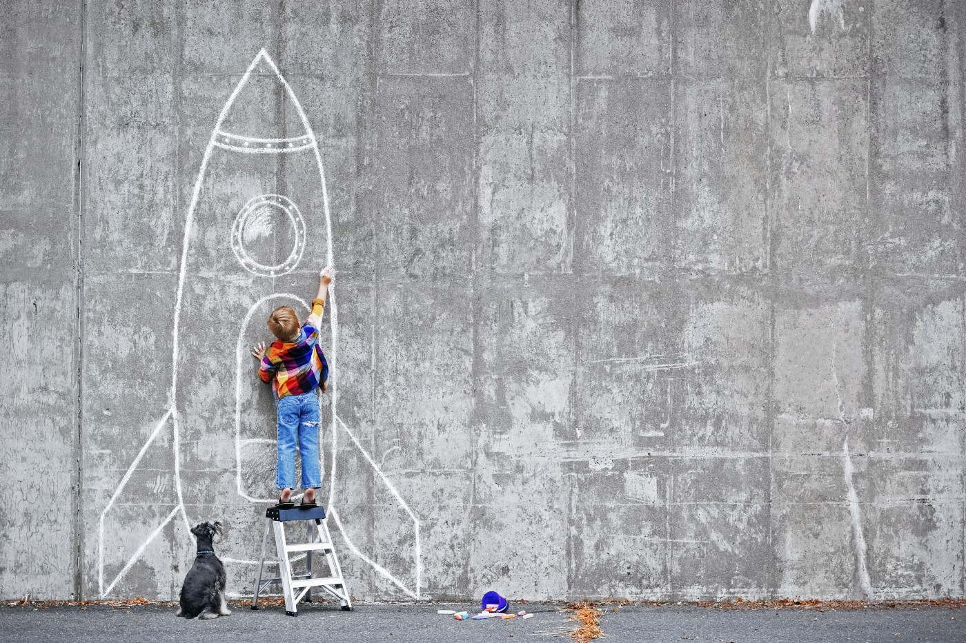 A young child stands on a short step ladder and uses white chalk to draw a rocket ship on a grey wall. A miniature schnauzer sits to the left of the child, watching.