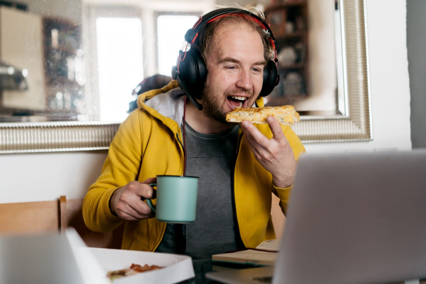 A photo of a man eating pizza and laughing while on a video call.