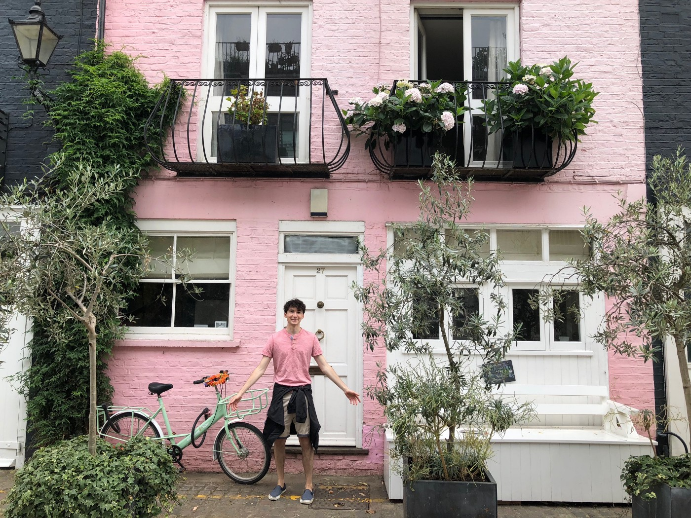 A boy in pink and black stands in front of a matching pink and black house with open arms. His name is Cole Tretheway.