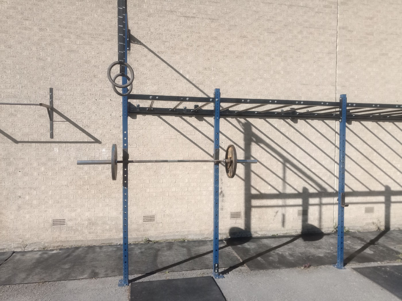 A metal squat rack with a loaded barbell