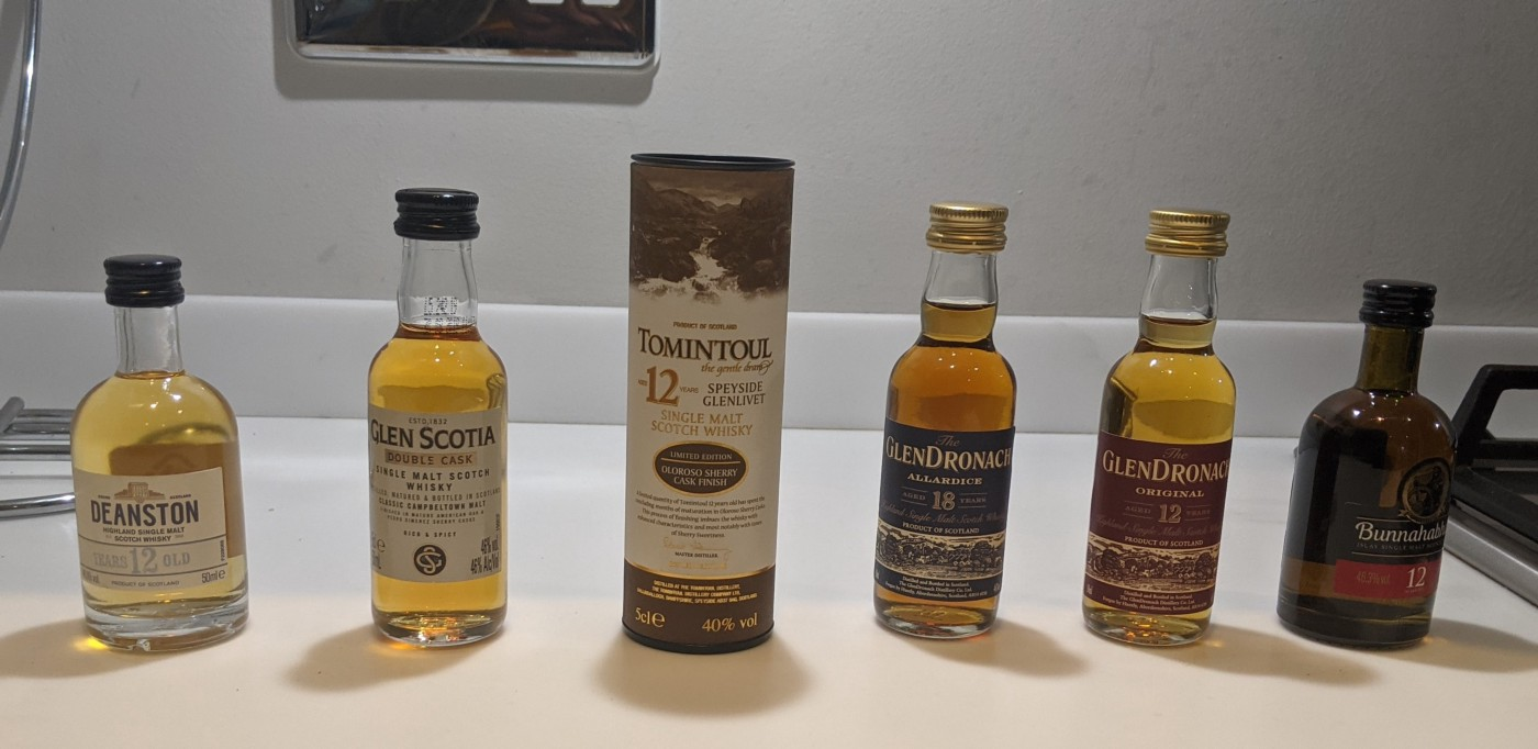 Six mini bottles of scotch. From left to right: Deanston's, Glen Scotia, Tomintoul 12, Glendronach 18, Glendronach 12, bunnahabhain 12
