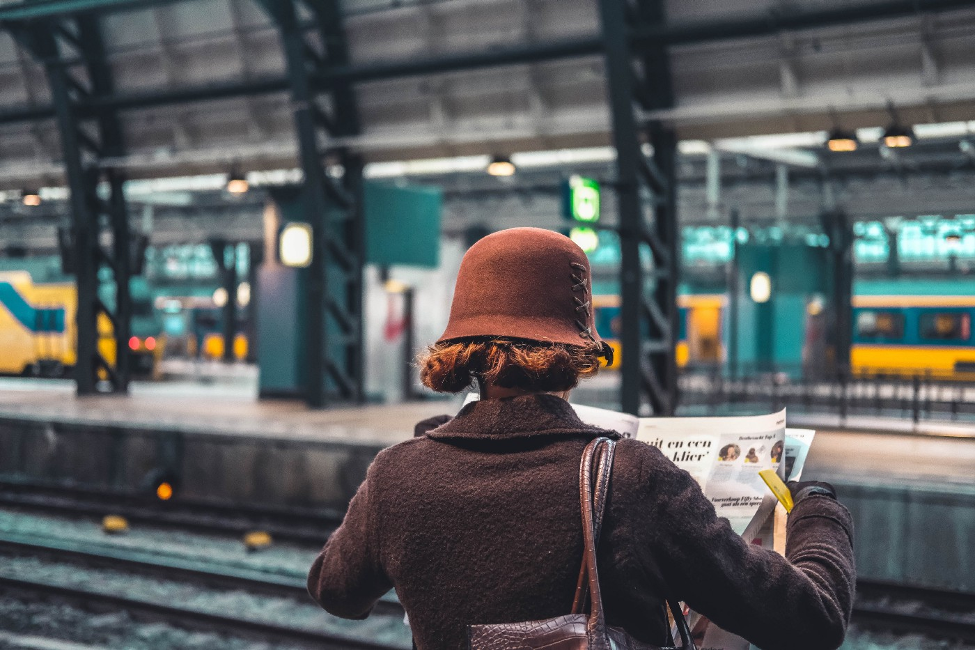 Woman reading newspaper waiting for train to arrive.