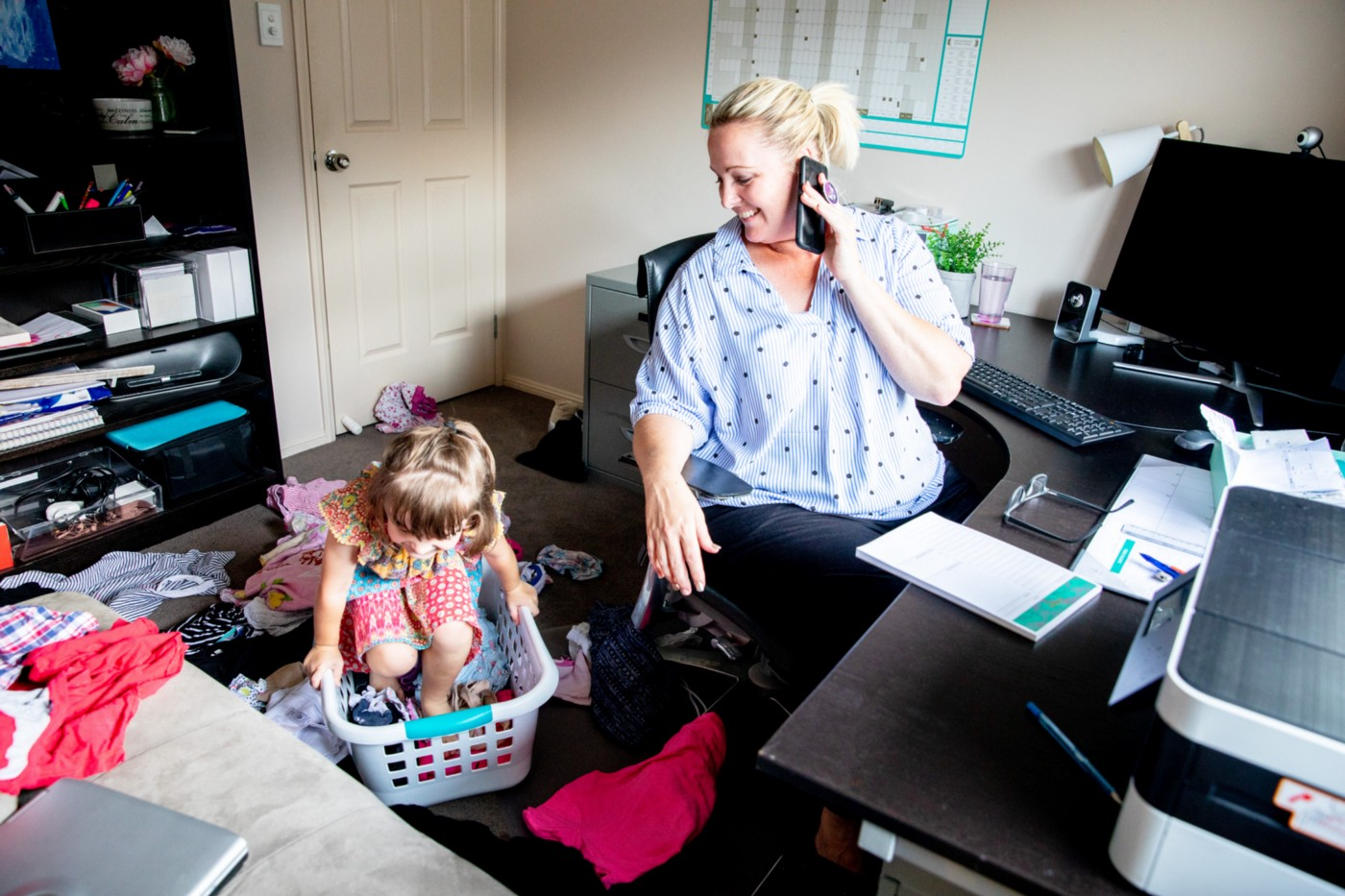 Mom works from home on the computer and phone while her daughter copies her and plays around her.